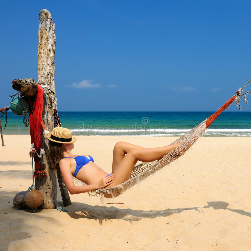 Woman in hammock on beach stock images