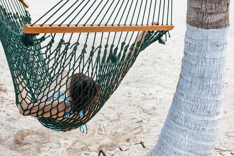 Woman in a hammock on the beach of Jamaica stock photo