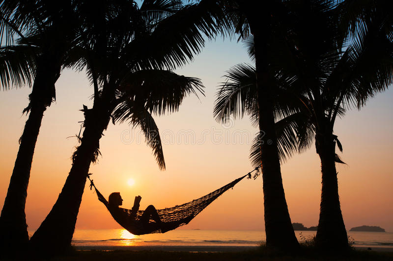 Woman in hammock on the beach royalty free stock image