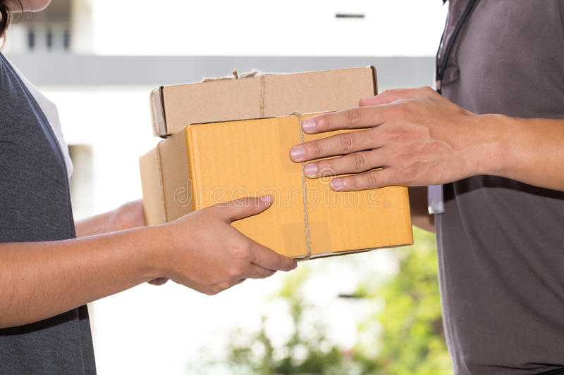 Woman hand accepting a delivery of boxes from deliveryman royalty free stock photos