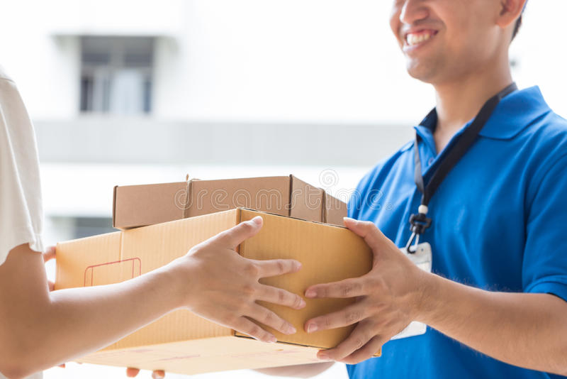 Woman hand accepting a delivery of boxes from deliveryman stock photography