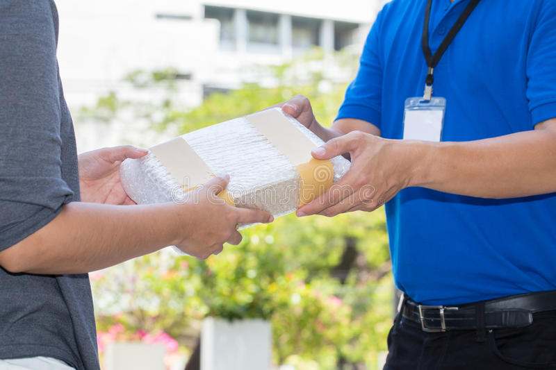 Woman hand accepting a delivery of shockproof boxes from deliver stock image