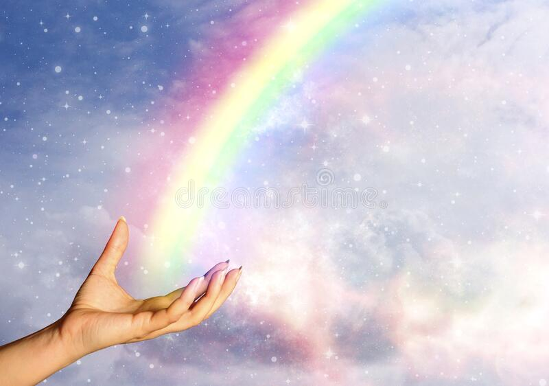 Woman hand with angelic rainbow, stars and beautiful sky royalty free stock photography