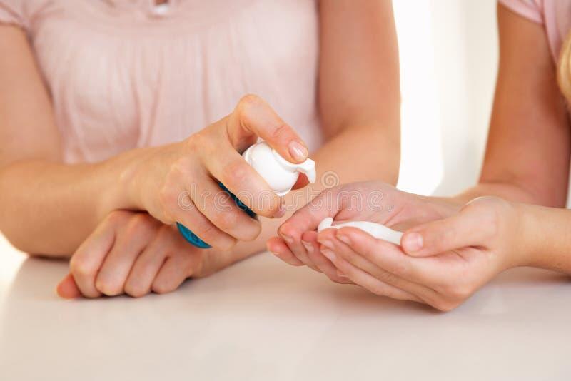 Woman hand applying hand sanitizer stock photography