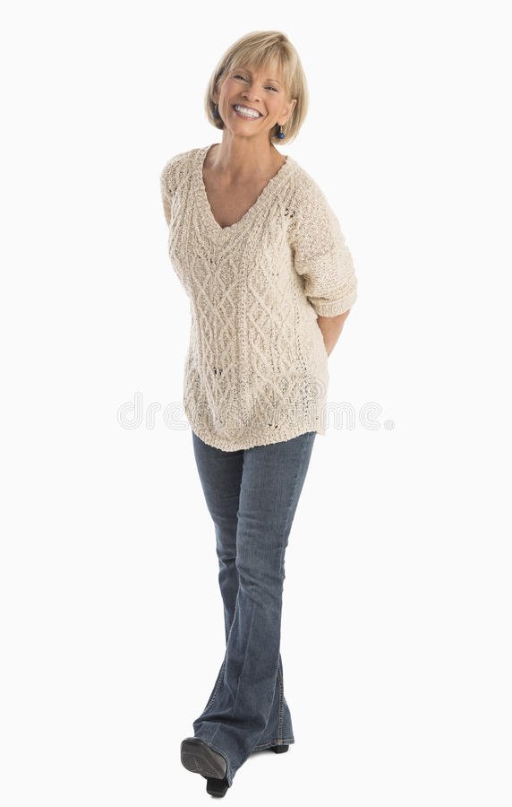 Woman With Hand Behind Back Walking Over White Background royalty free stock photography