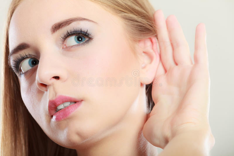 Woman with hand behind ear spying stock photography