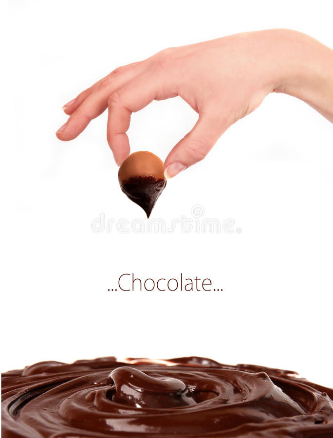 Woman hand with chocolate bonbon. Isolated on white background royalty free stock image