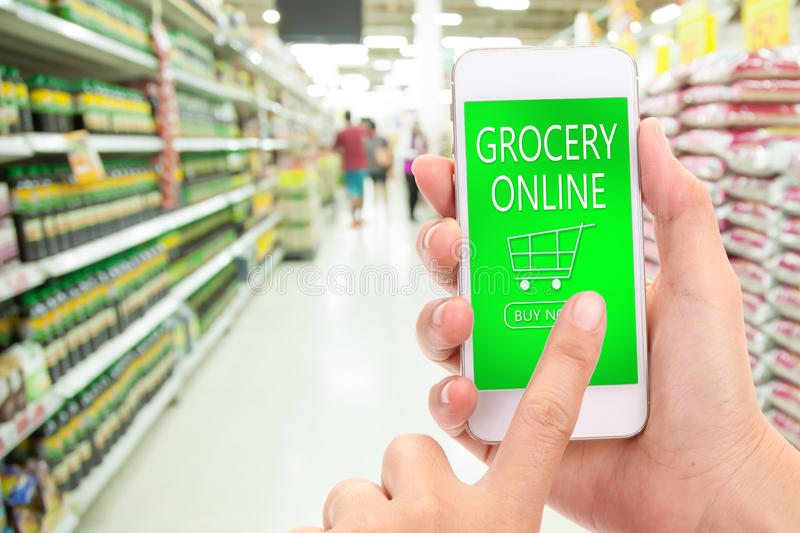 Woman hand click BUY NOW on mobile with blur supermarket background, Grocery online, delivery concept. royalty free stock photo
