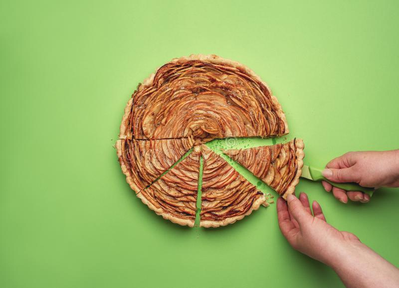 Woman hand cutting an apple pie. Home-baked sweets stock image