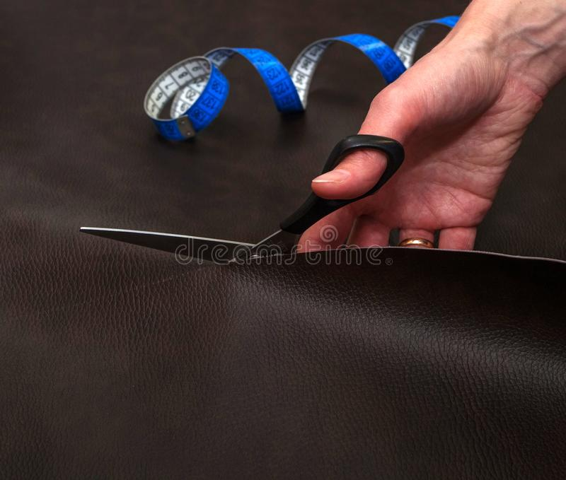 Woman cutting brown leather using scissors and twisted tape meas. Woman hand cutting brown leather using scissors and blue twisted tape measure, close up. Sewing stock photography