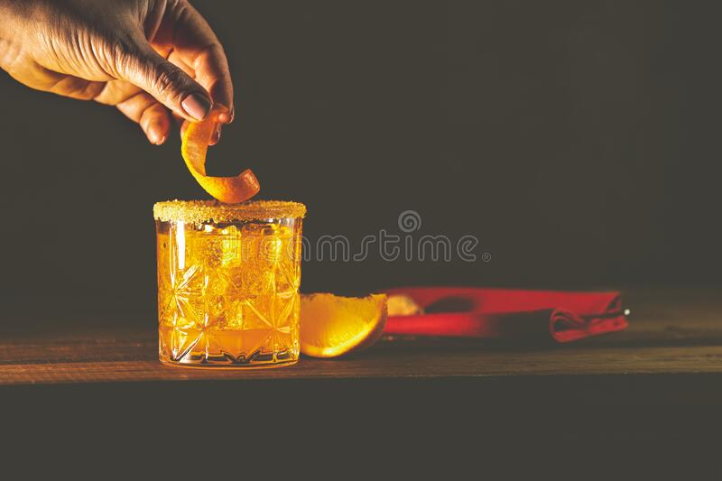 Woman hand decorate orange twist alcoholic cocktail negroni on old wooden board. Drink with gin, campari martini rosso and orange stock image