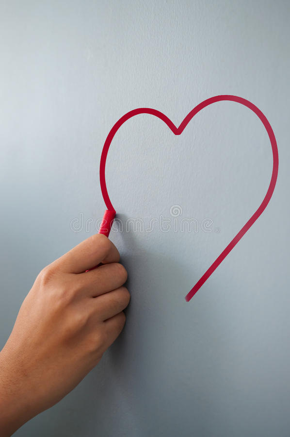 Woman hand drawing heart for valentines day with red chalk on w royalty free stock photo