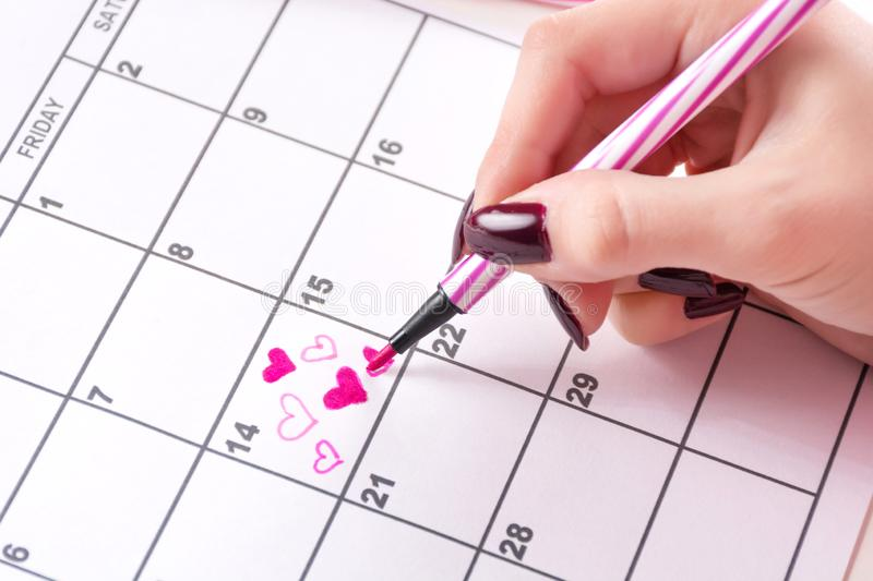 Woman hand drawing and paint heart in calendar with felt pen for Valentines day stock photo