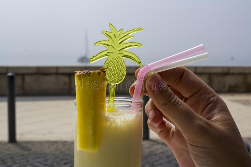 Woman hand drinking a pineapple smoothie cocktail at the beach stock photography
