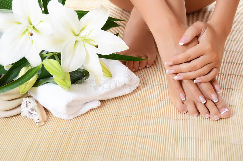 Woman hand and feet with manicure and Lily. Woman hand , feet with manicure and Lily close up royalty free stock images