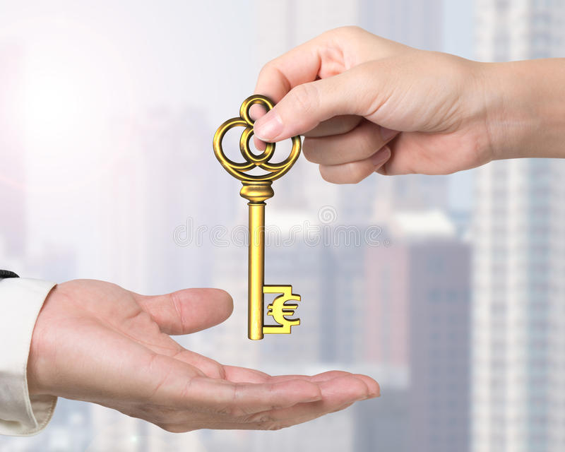 Woman hand giving Euro sign treasure key to man hand royalty free stock photo