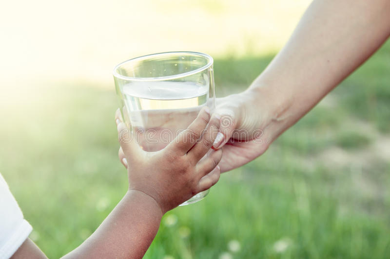 Woman hand giving glass of fresh water to child in the park stock photo