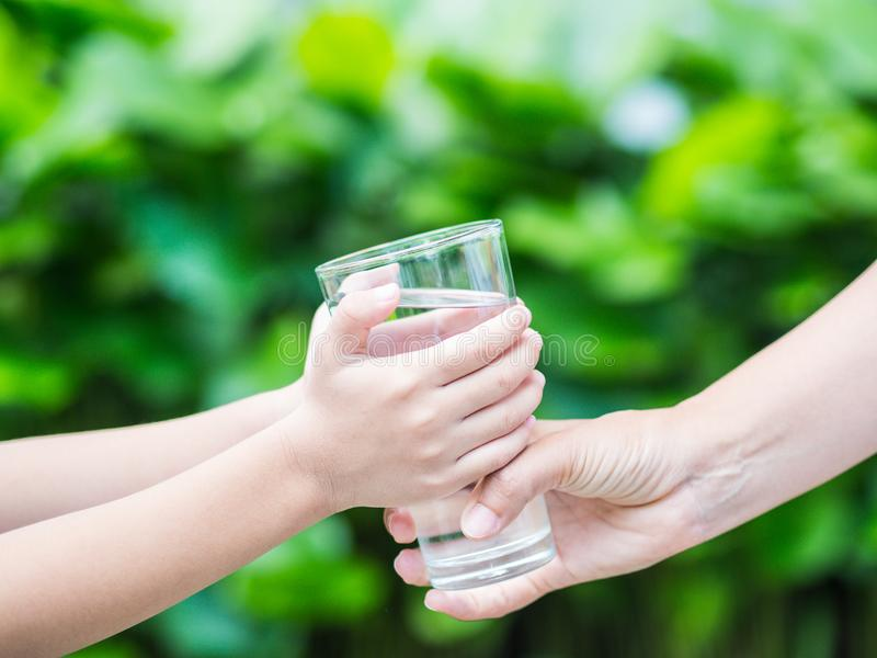 Woman hand giving glass of fresh water to child royalty free stock photography