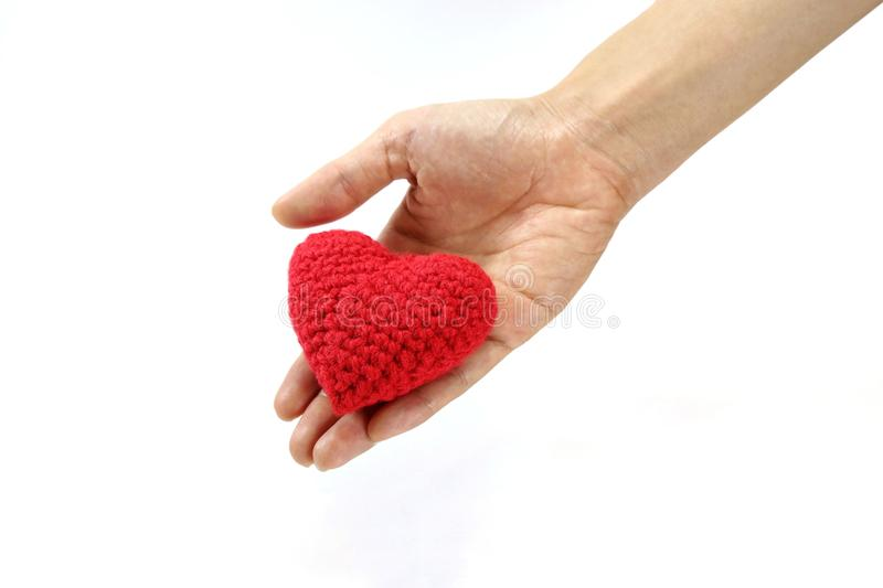 Woman hand giving red crocheted heart. Valentine`s Day. Symbol of love. Woman hand giving red crocheted heart. Valentine`s Day. Symbol and concept of love royalty free stock images