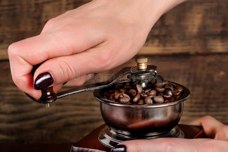 Woman hand grinding coffee roasted beans in retro mill and wooden background stock photography