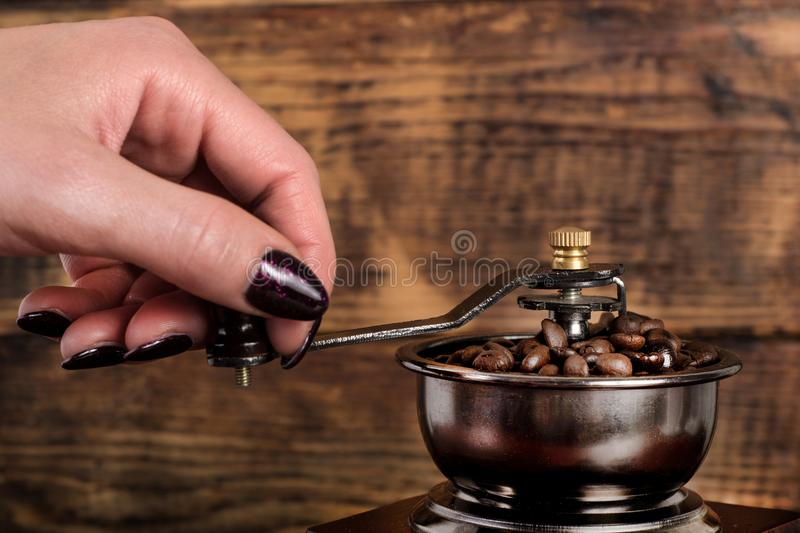 Woman hand grinding roasted coffee beans in mill royalty free stock photos