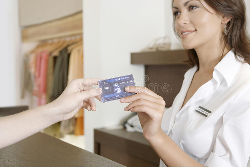 Woman Hand Handing Credit Card at Counter. Close up detail of customer's hand handing over credit card to a smiling store attendant stock photos