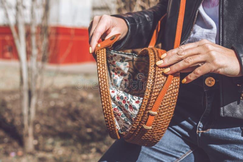 Woman hand with handmade organic rattan handbag. Rattan bag. Outdoors, Europe. Woman hand with handmade organic rattan handbag. Rattan bag royalty free stock photo