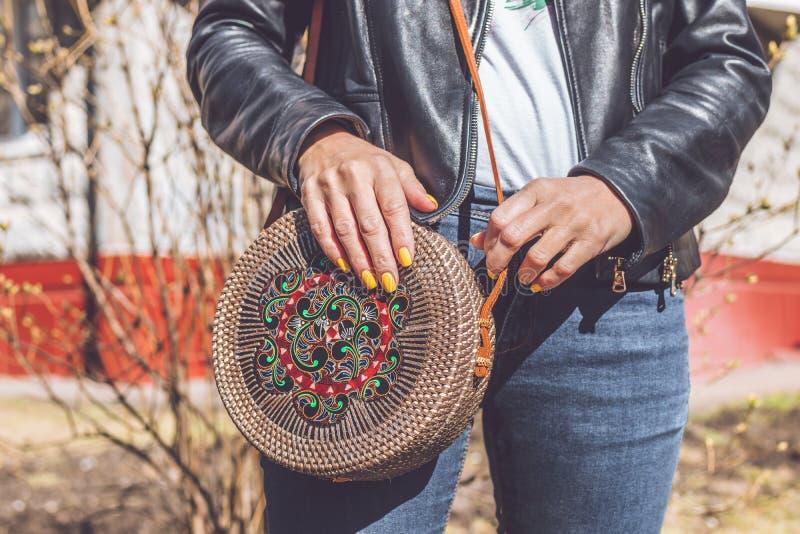 Woman hand with handmade organic rattan handbag. Rattan bag. Outdoors, Europe. Woman hand with handmade organic rattan handbag. Rattan bag royalty free stock image