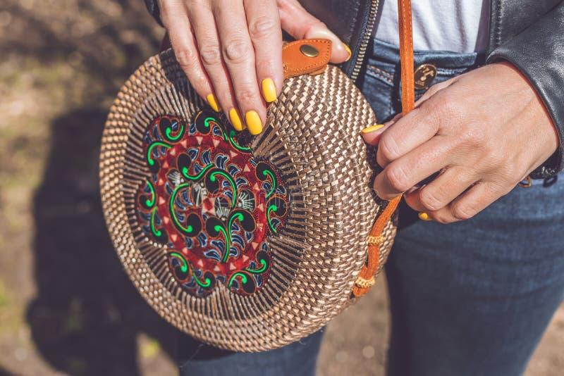 Woman hand with handmade organic rattan handbag. Rattan bag. Outdoors, Europe. Woman hand with handmade organic rattan handbag. Rattan bag stock photos