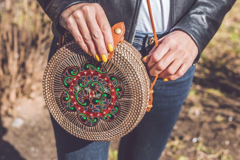 Woman hand with handmade organic rattan handbag. Rattan bag. Outdoors, Europe. Woman hand with handmade organic rattan handbag. Rattan bag stock images