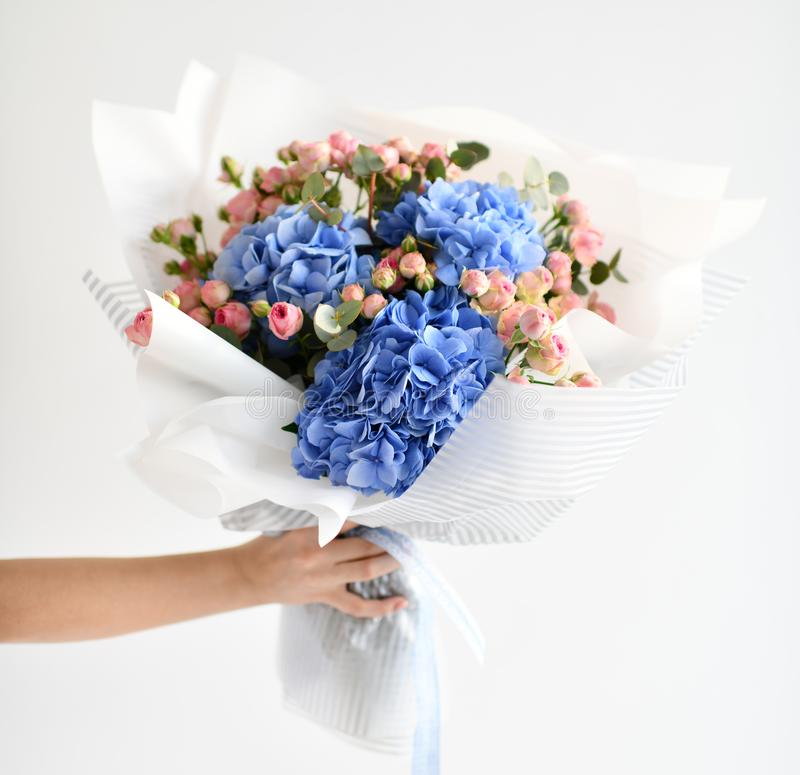 Woman hand hold bouquet of blue hydrangea flowers and pink roses royalty free stock photography