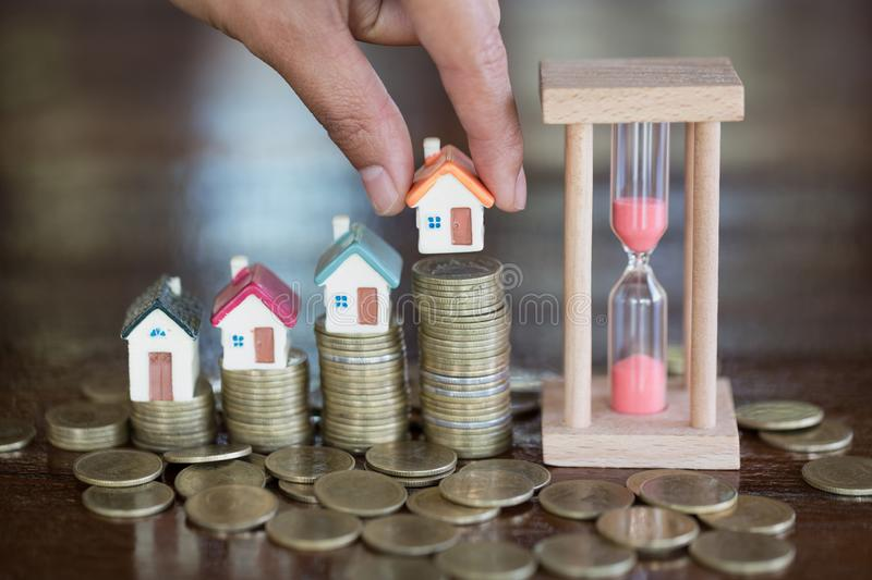 Woman hand hold a home model put on the stack coin with growing in the public park, Savings money for buy house and loan to stock photos