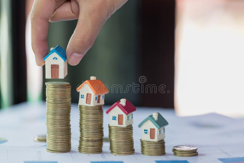 Woman hand hold a home model put on the stack coin with growing, Savings money for buy house and loan to business investment for. Real estate concept. Invesment royalty free stock images