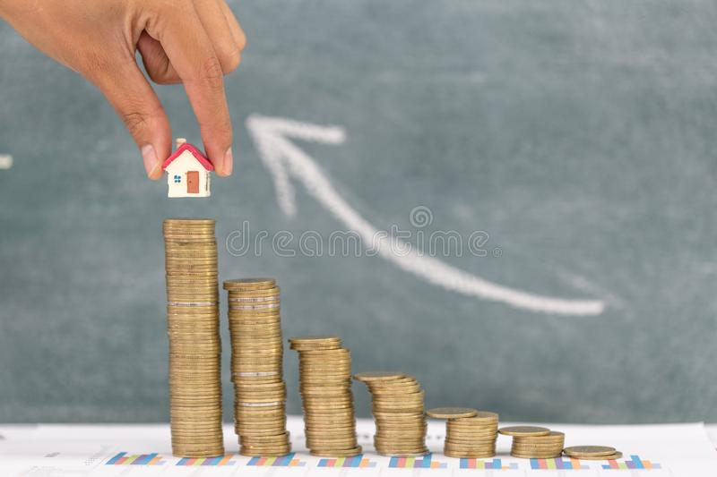Woman hand hold a home model put on the stack coin with growing, Savings money for buy house and loan to business investment for. Real estate concept. Invesment stock image