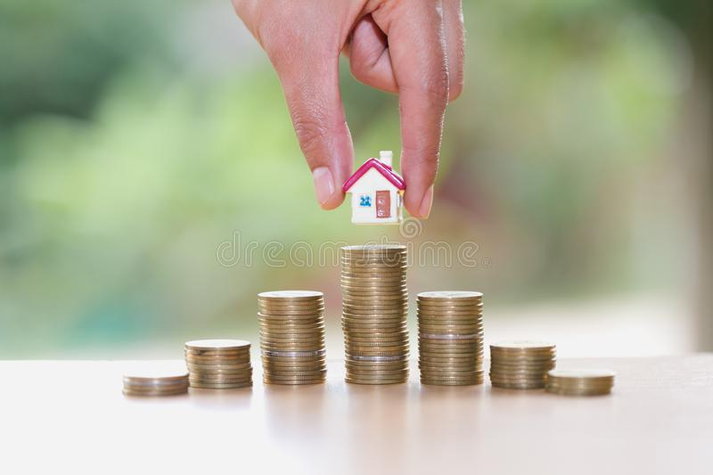 Woman hand hold a home model put on the stack coin with growing, Savings money for buy house and loan to business investment for. Real estate concept. Invesment stock images