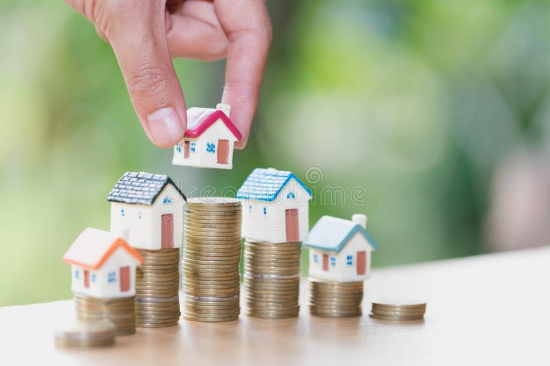 Woman hand hold a home model put on the stack coin with growing, Savings money for buy house and loan to business investment for. Real estate concept. Invesment stock photography
