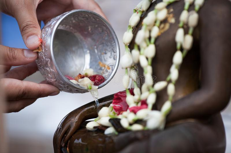 Woman hand hold little bowl to bath Buddha statue. For blessing ceremony celebrate Songkran in new year water festival, Thai culture concept stock photography