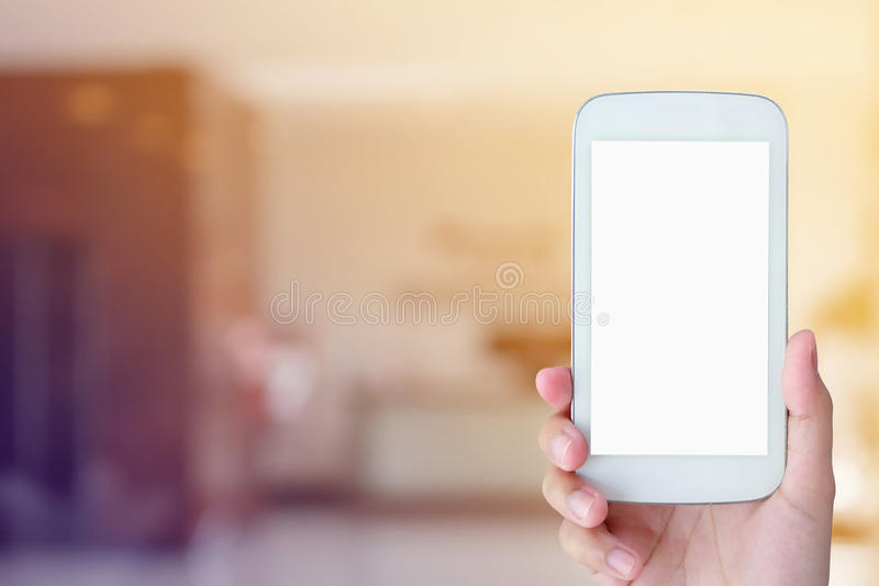Woman hand hold mobile smartphone with hotel lobby royalty free stock images