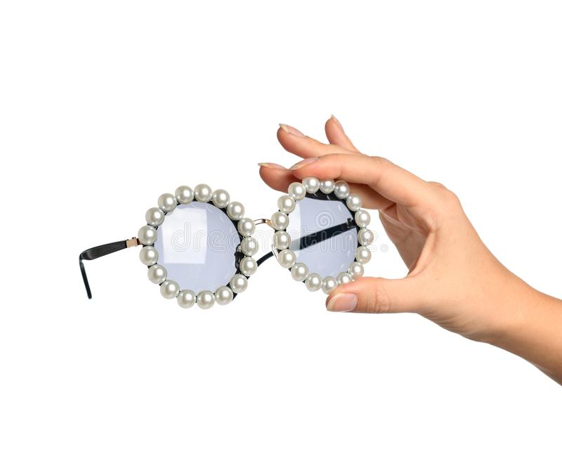 Woman hand hold modern round sunglasses with pearl isolated on a white stock photos