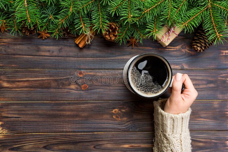 Woman hand hold Mug of coffee on black wooden christmas background. top view, copy space royalty free stock photos