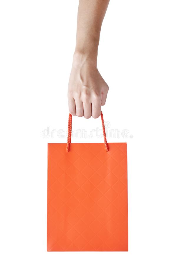 Woman hand hold red empty blank craft paper shopping bag isolated on white background. Packaging template mockup royalty free stock image
