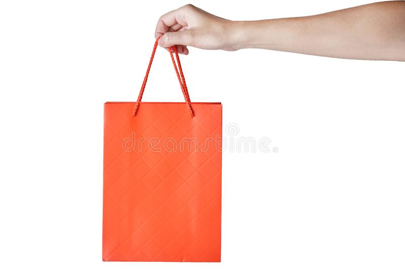 Woman hand hold red empty blank craft paper shopping bag isolated on white background. Packaging template mockup stock image