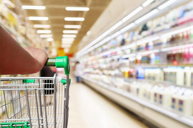 Woman hand hold supermarket shopping cart with abstract blur refrigerator shelves stock photos