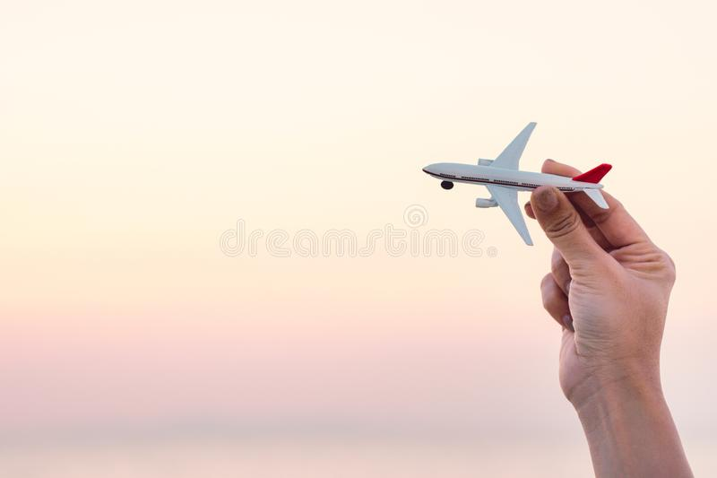 Woman hand holding airplane model in sunset sky and summer sea b royalty free stock photos