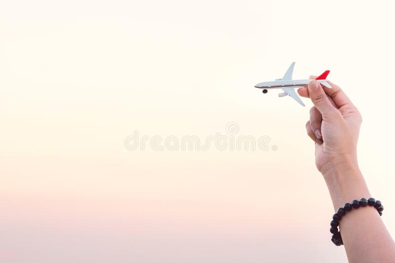 Woman hand holding airplane model in sunset sky and summer sea b stock photo