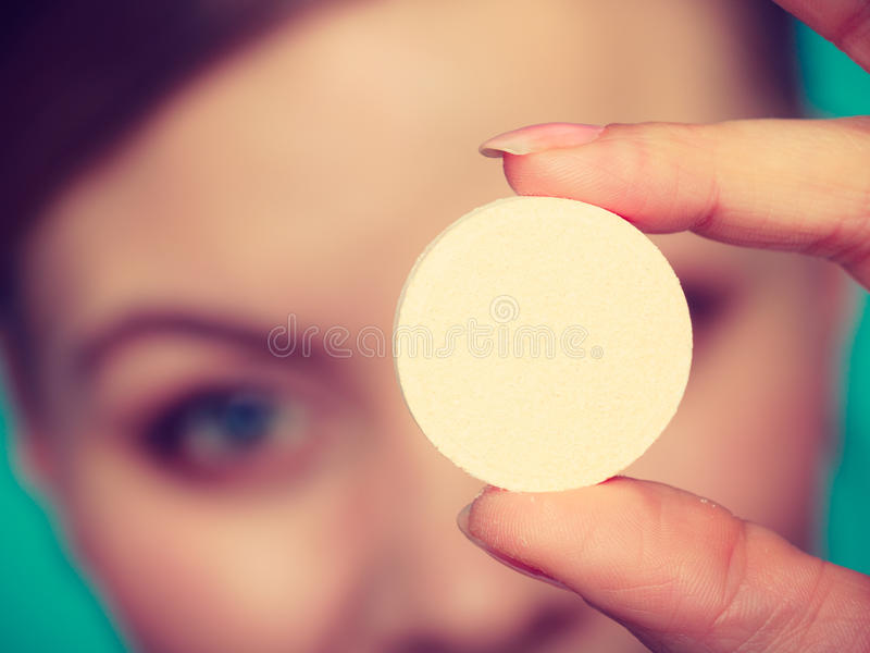 Woman hand holding big effervescent pill. Vitamins, health, medicines. Woman holding behing her face big supplement effervescent tablet packed in tin foil royalty free stock image