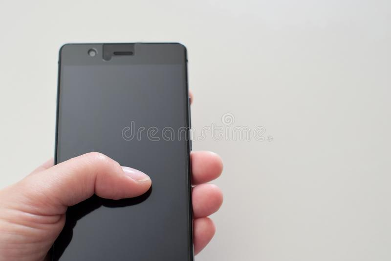 Woman hand holding black smartphone stock image