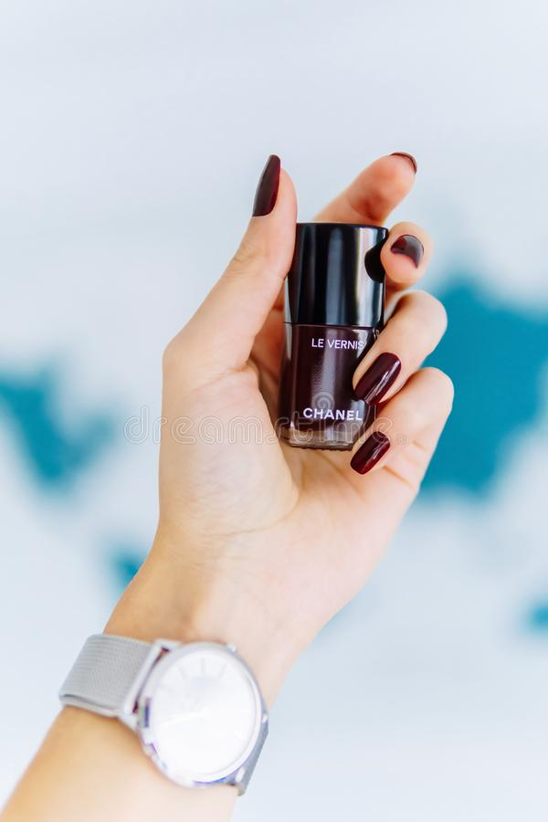 Woman Hand Holding A Bottle Of Chanel Rouge Noir Nail Polish stock photography