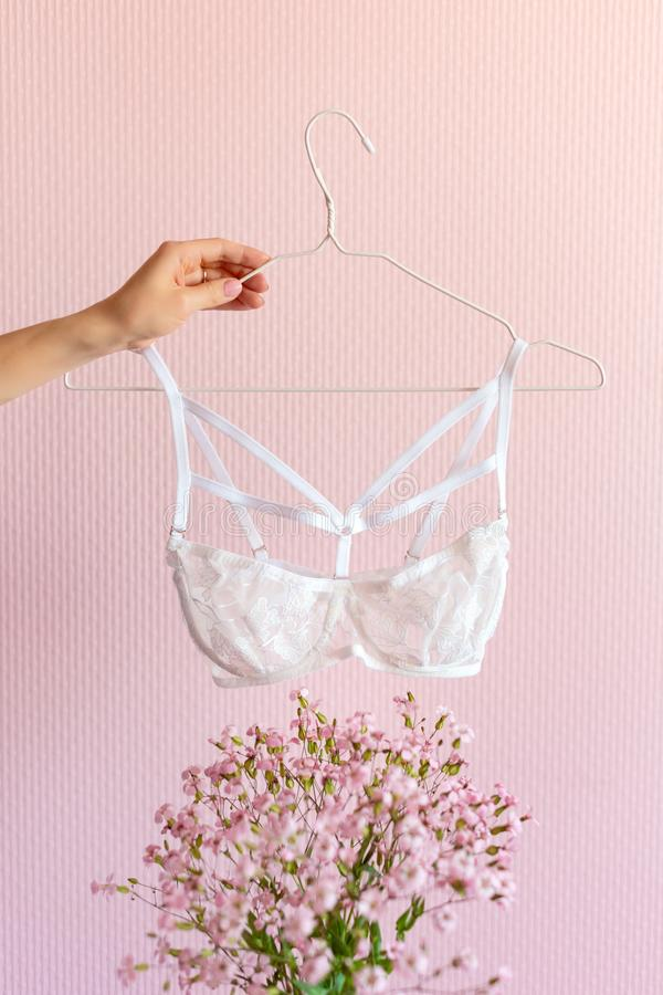 Woman hand holding bra on pink background with flowers. Lingerie in hands, fashion and sale concept. Woman hand holding bra on pink background with flowers royalty free stock images