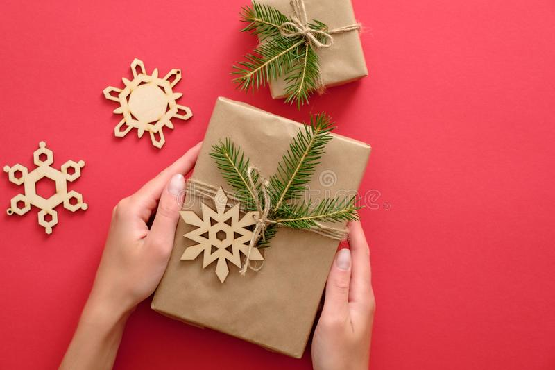 Woman hand holding Christmas present wrapped kraft paper, fir branches, wooden handmade snowflake on red background. Flat lay, top royalty free stock photos